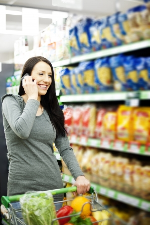Beautiful woman on mobile phone at supermarket photo