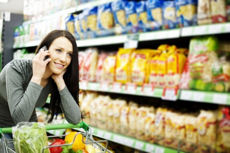 Beautiful woman on mobile phone at supermarket Stock Photo - 18161230