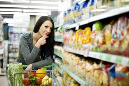 carro supermercado: Mujer en la tienda de abarrotes Foto de archivo