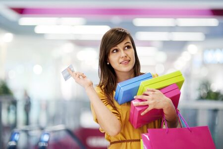 three presents: Beautiful woman with credit card in shopping mall