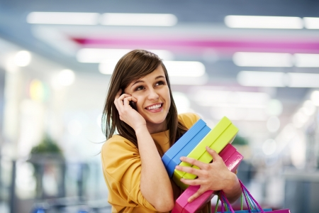 Beautiful woman on the phone in shopping mall photo