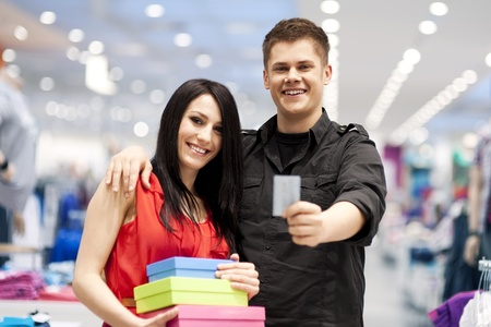 Happy young couple spending money at clothing store photo
