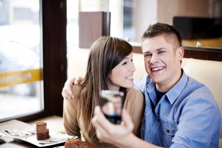 pareja comiendo: Pareja de tomar la fotografía en el café