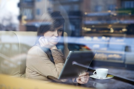 shop window: Young woman using tablet in coffee shop Stock Photo