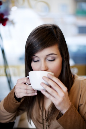 Close up of woman drinking coffee photo