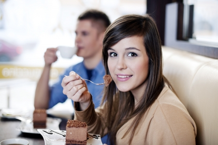 Young woman eating chocolate cake photo
