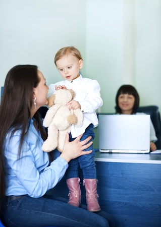 Mother entertaining her daughter at doctors office photo