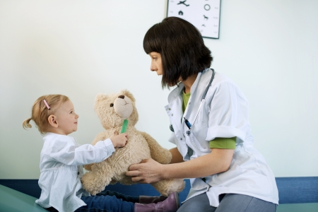 Pediatrician playing with child at doctors office photo