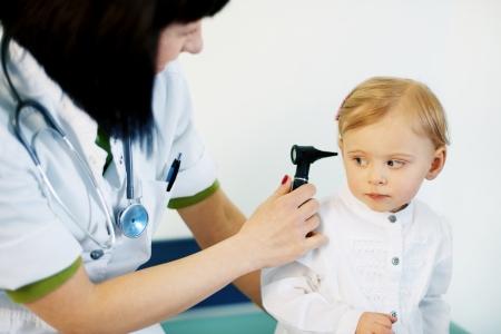 otoscope: Pediatrician doing ear exam of baby girl Stock Photo