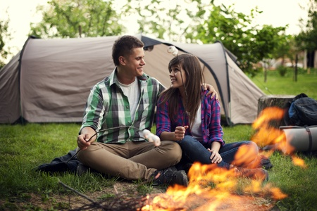 Young couple sitting near a campfire and toasting marshmallow photo