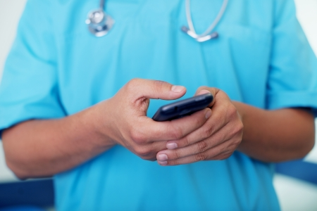 doctor surgeon: Doctor texting on mobile phone Stock Photo