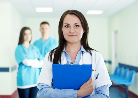 medical worker: Portrait of young female doctor with interns in background Stock Photo