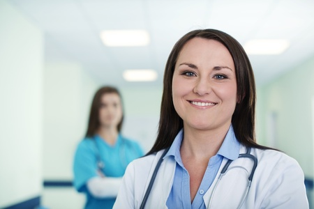 Portrait of young female doctor with intern in background Stock Photo - 18182350