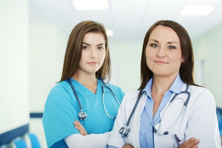 Portrait of young female doctor with intern in background Stock Photo - 18182349