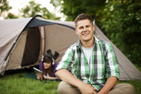 chill out: Young man sitting in front of tent