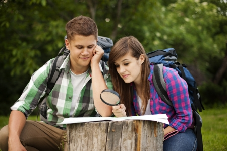 explorer man: Young couple with map in forest