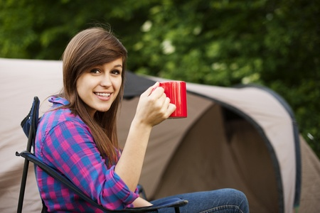 camping: Young woman sitting in front of the tent Stock Photo