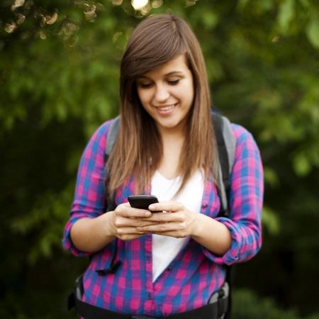 Beautiful female hiker texting photo