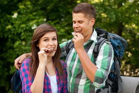 Young couple eating chocolate in forest photo