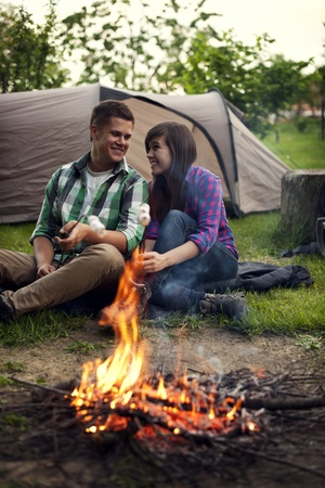 camping tent: Young couple sitting near a campfire and toasting marshmallow