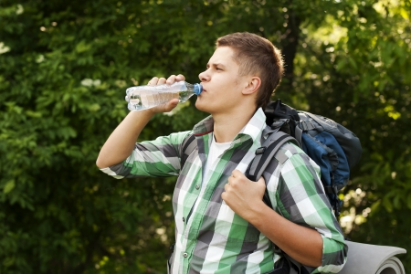 Hiker drinking water in forest photo