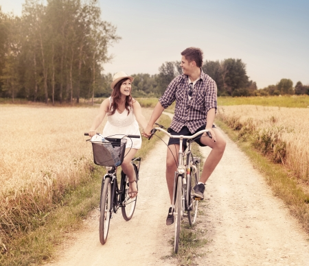 adult dating: Happy couple cycling outdoors in summer Stock Photo