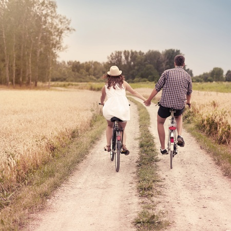 couple holding hands: Romantic cycling Stock Photo