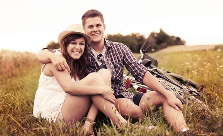 Couple resting on grass after biking photo