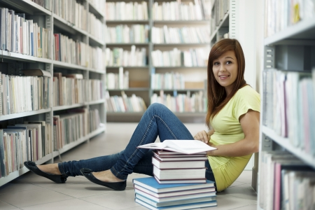 studying: Beautiful student in library Stock Photo