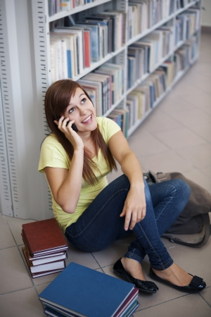 Happy student on the phone in library photo