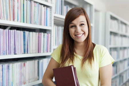 university building: Cheerful student girl holding books in library