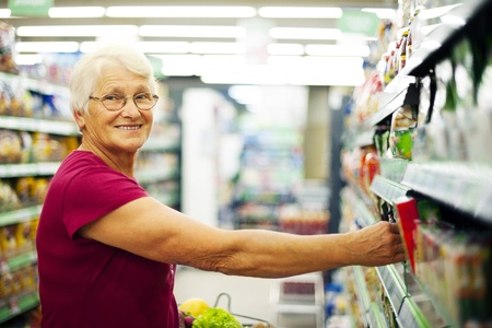 Happy senior woman at supermarket photo