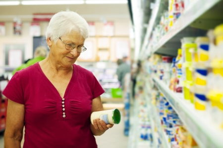 product packaging: Senior woman checking label on jar