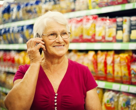 Senior woman on the phone at supermarket photo