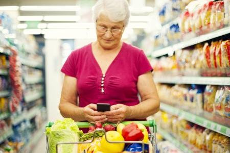 tiendas de comida: Mujer mayor que los mensajes de texto en el tel�fono m�vil en el supermercado
