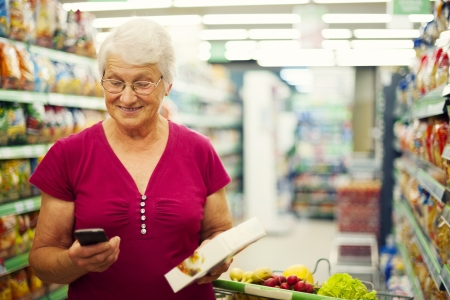 Senior donna di SMS sul cellulare in supermercato photo