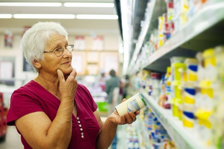 a jar stand: Senior woman at groceries store