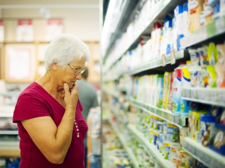 dairy products: Senior woman choosing a dairy products at supermarket