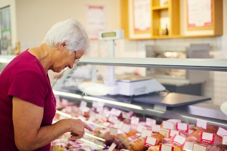 Senior woman in butchers shop    photo