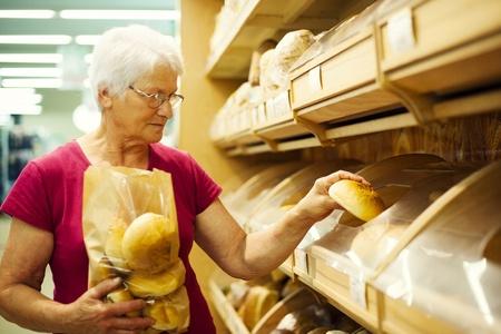 bakery store: Senior woman packing buns at supermarket