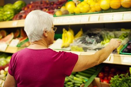 reach customers: Senior woman at supermarket