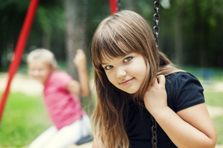 8 years: Little girl smiling on swing