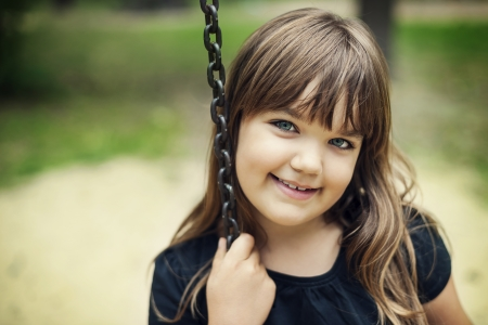 Portrait of smiling girl on swing photo