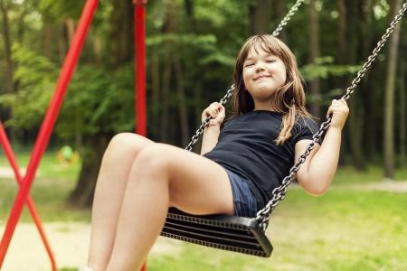 columpios: Muchacha que se divierte en el oscilaci�n