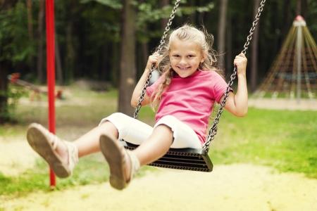 baby girls smiley face: Happy girl swinging on playground