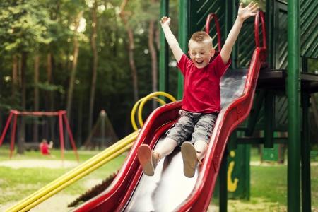 children playground: Active boy sliding down