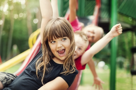niños en area de juegos: Los niños se divierten en la diapositiva
