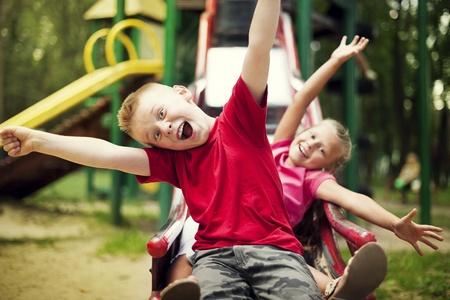 Two kids slide on playground Stock Photo