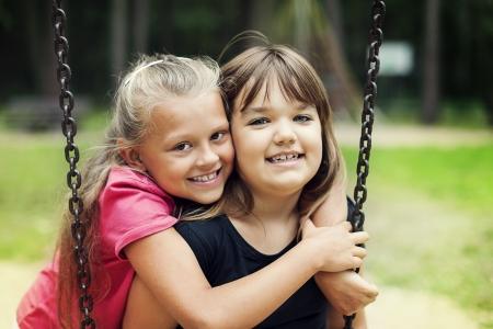 8 9 years: Best friends swinging in a park