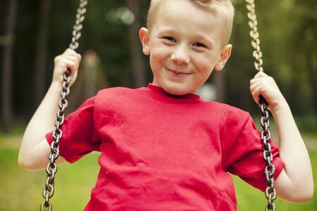 8 9 years: Close-up of little boy swinging Stock Photo